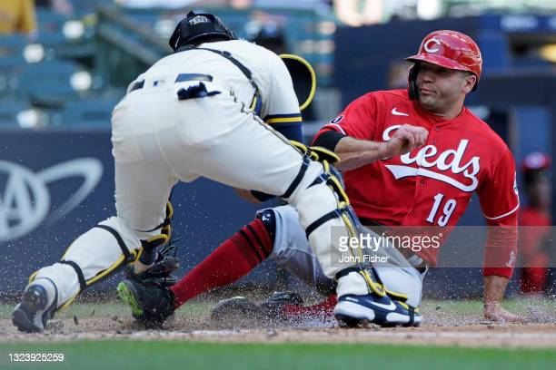 Joey Votto of the Cincinnati Reds slides safely into home plate in the seventh inning against the Milwaukee Brewers at American Family Field on June...