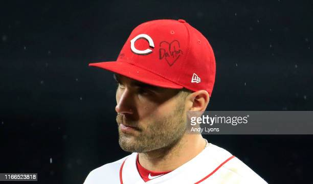 Joey Votto of the Cincinnati Reds wears a hat with a message in memory of victims of Sunday's mass shooting in Dayton Ohio during the game against...