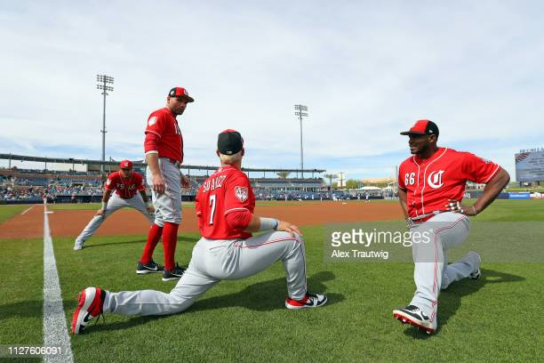 Joey Votto Yasiel Puig and Eugenio Suarez of the Cincinnati Reds stretch ahead of a Spring Training game against and the Seattle Mariners on Monday...