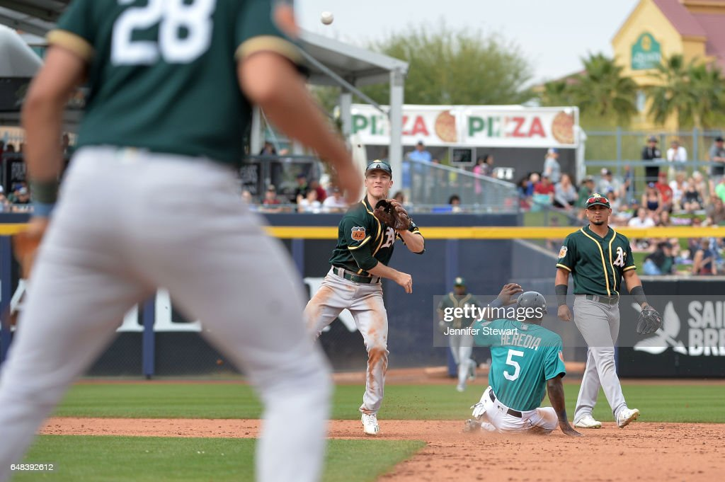 Joey Wendle #52 of the Oakland Athletics turns the double play over Guillermo Heredia #5 of the Seattle Mariners during the spring training game at Peoria Stadium on March 5, 2017 in Peoria, Arizona.