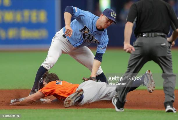 Joey Wendle of the Tampa Bay Rays applies a tag to Jake Marisnick of the Houston Astros to complete a strikeout - tag out double play in the sixth...