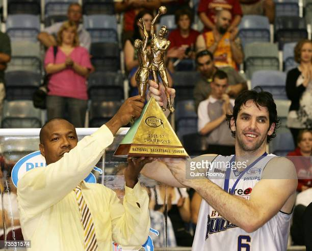 Joey Wright the coach and Sam MacKinnon the captain of the Bullets raise the trophy after winning game four of the NBL Grand Final Series between the...
