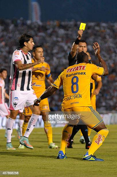 Joffre Guerron of Tigres reacts after being yellow carded by referee Jorge Antonio Perez during a match between Monterrey and Tigres UANL as part of...