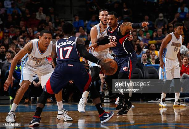 Joffrey Lauvergne of the Denver Nuggets defends against Mike Scott of the Atlanta Hawks as Erick Green of the Denver Nuggets guards Dennis Schroder...