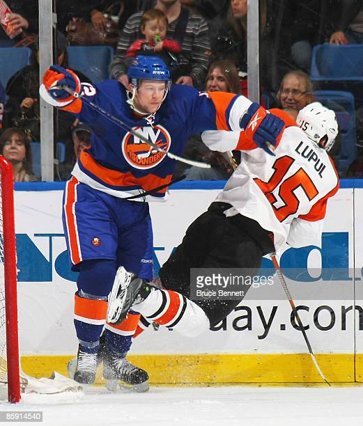 Joffrey Lupul of the Philadelphia Flyers is pushed off his skates by Josh Bailey of the New York Islanders on April 11 2009 at the Nassau Coliseum in...