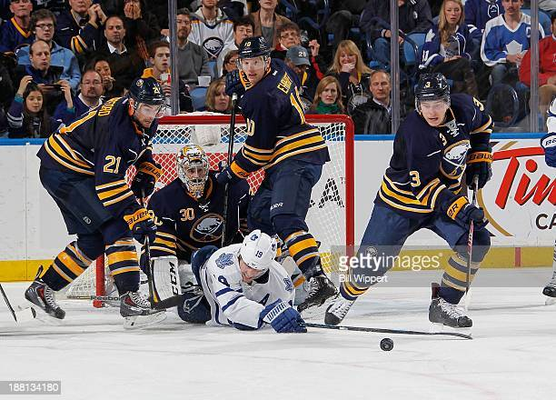 Joffrey Lupul of the Toronto Maple Leafs gets upended in front of goaltender Ryan Miller of the Buffalo Sabres while being defended by Drew Stafford...
