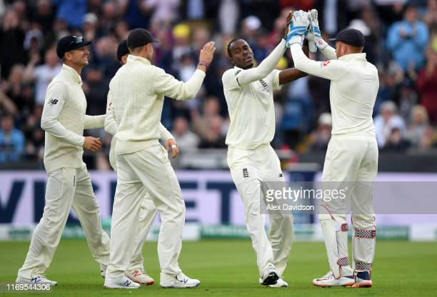 Jofra Archer of England celebrates taking the wicket of Marcus Harris of Australia with Jonny Bairstow and Joe Root of England during Day One of the...