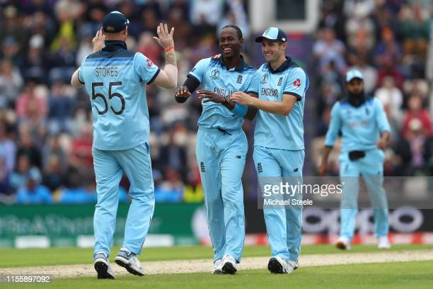Jofra Archer of England celebrates with Chris Woakes and Ben Stokes after taking the wicket of Sheldon Cottrell during the Group Stage match of the...