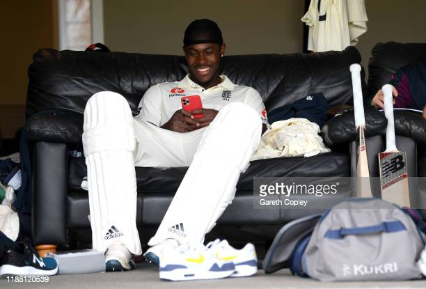 Jofra Archer of England looks at his phone before going out to bat during day three of the tour match between New Zealand A and England at Cobham...