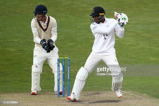 Jofra Archer of Sussex hits out while Surrey wicket keeper Billy Mead looks on during the Second Eleven Championship match between Sussex 2nd XI and...