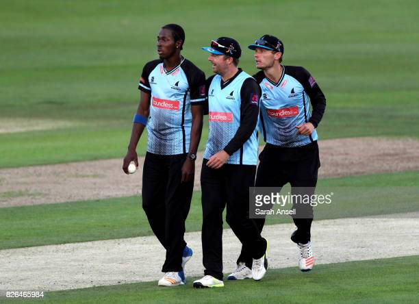 Jofra Archer of Sussex Sharks is congratulated by teammates captain Chris Nash and Danny Briggs after taking the wicket of Matt Coles of Kent...