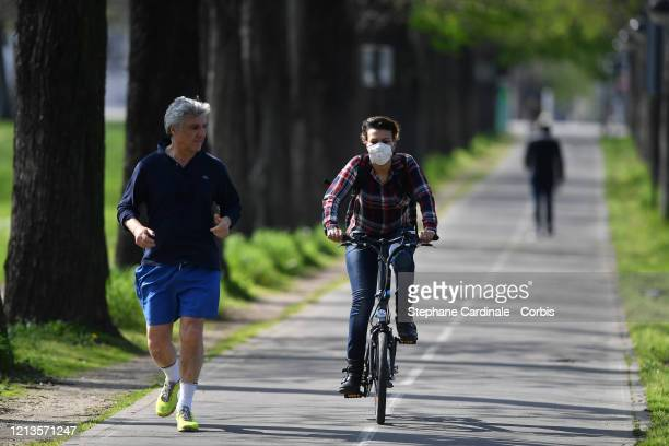 A jogger and a woman wearing a protective mask who rides her bicycle are seen the third day after the announcement by French President Emmanuel...