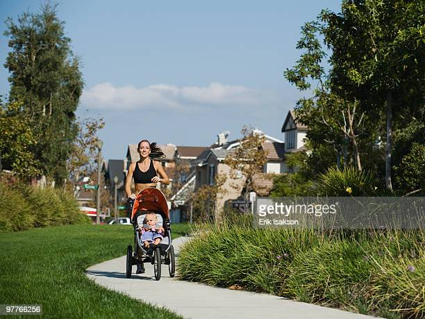 jogger and baby - three wheeled pushchair stock pictures, royalty-free photos & images