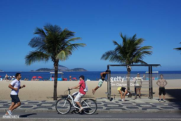 A jogger and cyclist pass a fitness workstation on the edge of Ipanema Beach Rio de Janeiro Brazil 4th July 2010