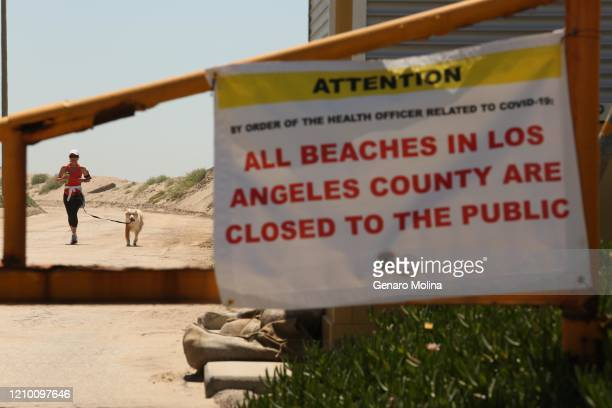 Jogger and her dog run on a closed Westward Beach Road during days of the coronavirus pandemic at Westward Beach in Malibu on Wednesday, April 15,...