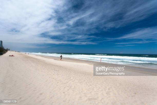 Jogger and sunbather on beach in Brisbane