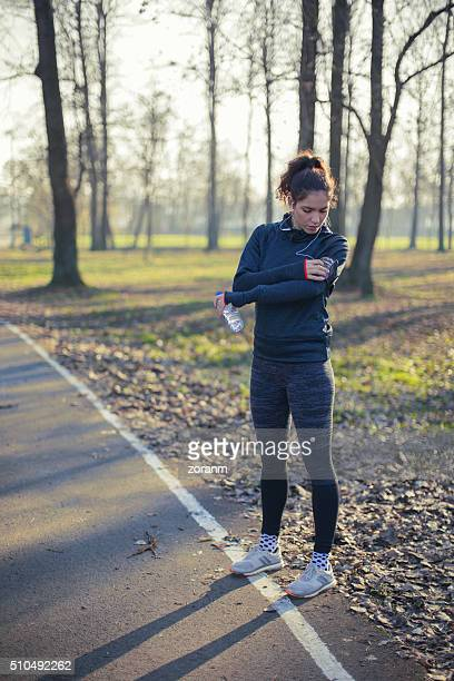 Jogger choosing music from smart phone