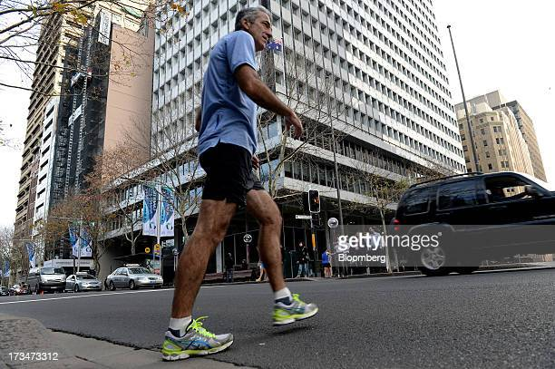 A jogger crosses the road in front of the Reserve Bank of Australia headquarters in the central business district of Sydney Australia on Monday July...