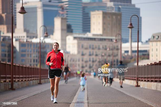 jogger crossing minneapolis' famous stone arch bridge. - minneapolis stock photos and pictures