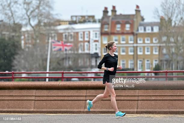 Jogger exercises beside the River Thames in Battersea Park in London on March 28, 2021. - From Monday, England's stay-at-home order to combat the...