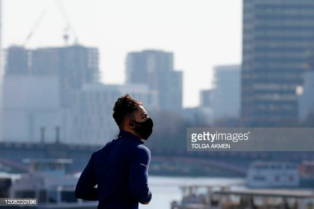 Jogger in a mask runs along Westminster Bridge in a quiet central London on March 25 after Britain's government ordered a lockdown to slow the spread...