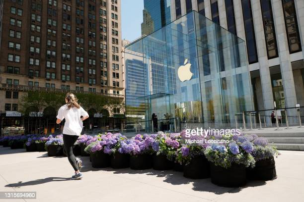 Jogger jogs past the Fifth Avenue Blooms Mother's Day installation in front of The Apple store on May 01, 2021 in New York City.