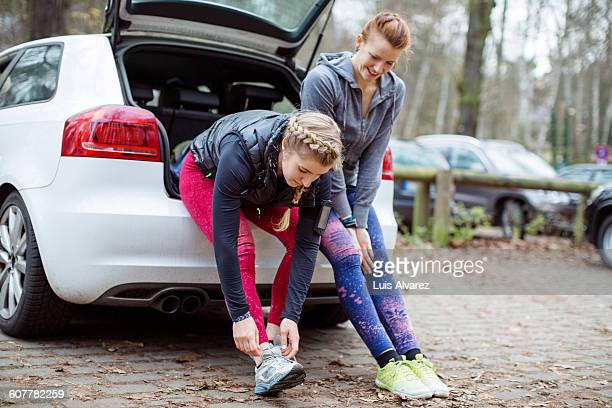Jogger looking at friend wearing shoe on car trunk