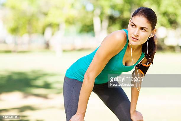 Jogger Looking Away While Listening Music On Earphones In Park