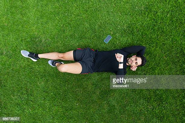 Jogger lying in grass looking on watch