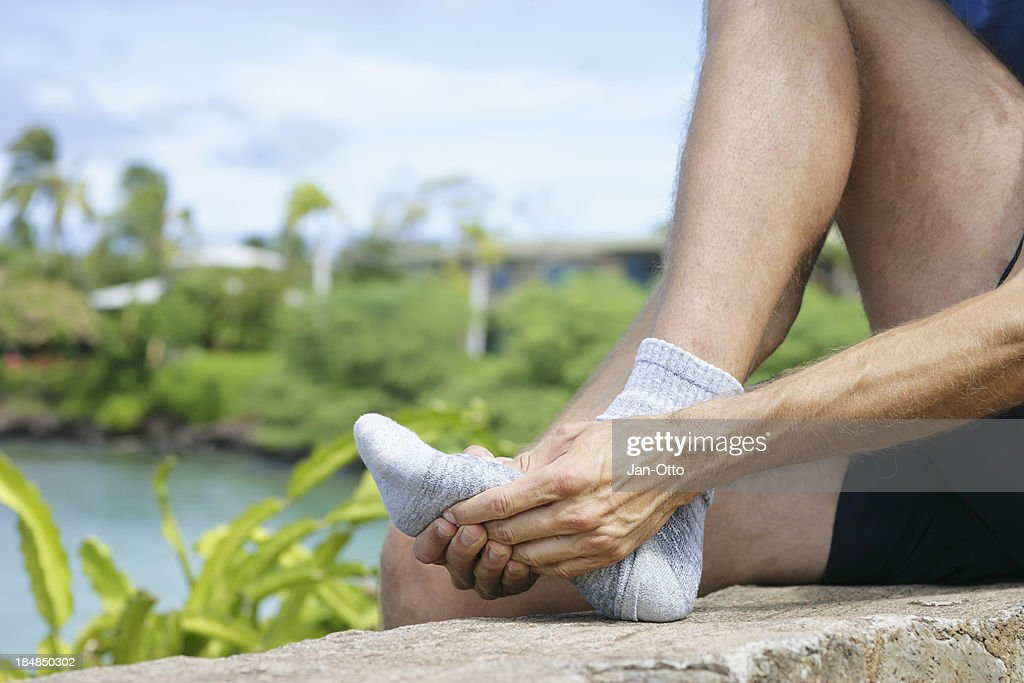 Jogger massaging the metatarsal area of the foot : Stock Photo