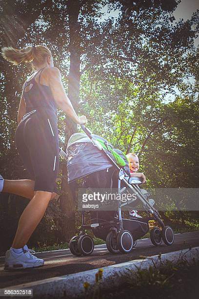 jogger mom with baby in stroller - mid adult stock photos and pictures