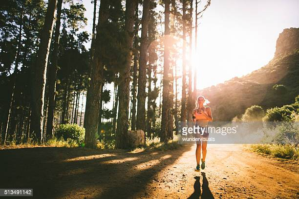 jogger on a dirt path on a mountain nature trail - cross country running stock pictures, royalty-free photos & images