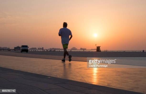jogger on a purpose built walking/running track on a beach in dubai at sunset - claire plumridge stock pictures, royalty-free photos & images