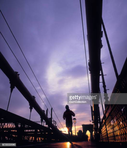 Jogger on Brooklyn Bridge in New York at sunrise