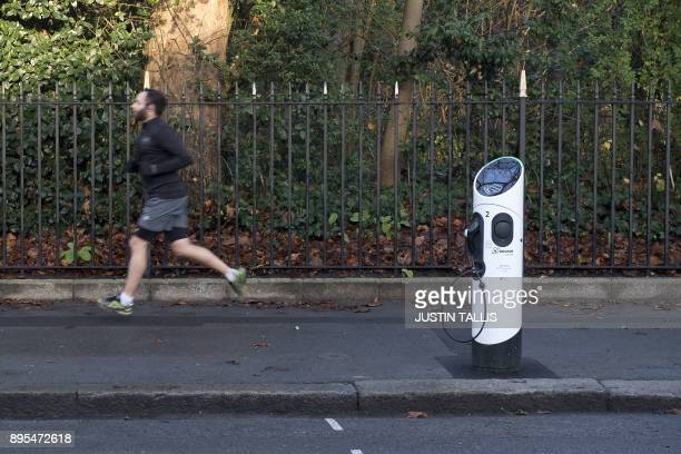 A jogger passes a Source London electric vehicle charging point in London on December 19 2107 / AFP PHOTO / Justin TALLIS