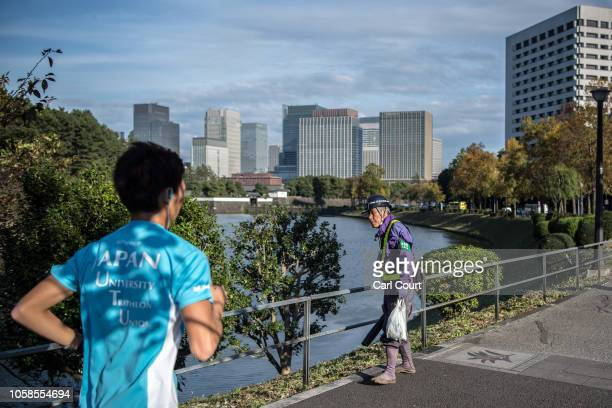 A jogger passes a worker clearing leaves by the moat surrounding the Imperial Palace on November 7 2018 in Tokyo Japan