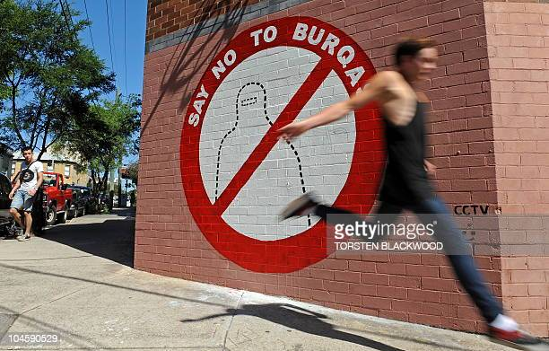 A jogger passes Australian artist Sergio Redegalli's antiburqa mural on the wall of his studio in Sydney on September 30 2010 Sergio's studio has...