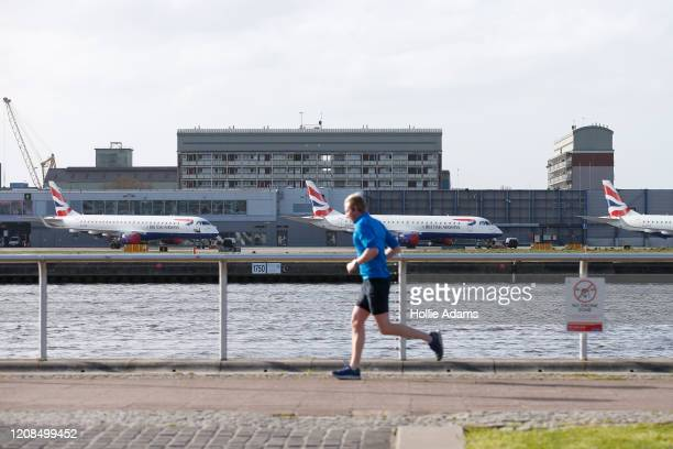 Jogger passes grounded aeroplanes at London City Airport on March 29, 2020 in London, England. The field hospital will initially contain 500 beds...