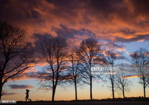 A jogger passes under brilliant skies as the sun sets at Back Cove in Portland on Wednesday Nov 29 2107