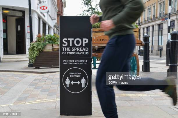 Jogger passing by a covid-19 warning sign in Covent Garden, Central London. Covid-19 cases continue to drop in the UK, as the government continues to...