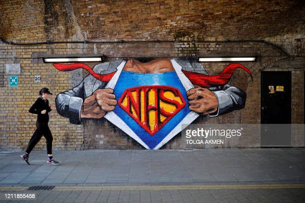 A jogger psses an artwork celebrating the National Health Service painted on a brick wall in central London on May 5 during the nationwide lockdown...
