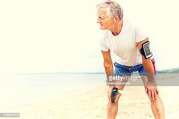 jogger resting after running - fat man on beach stock photos and pictures