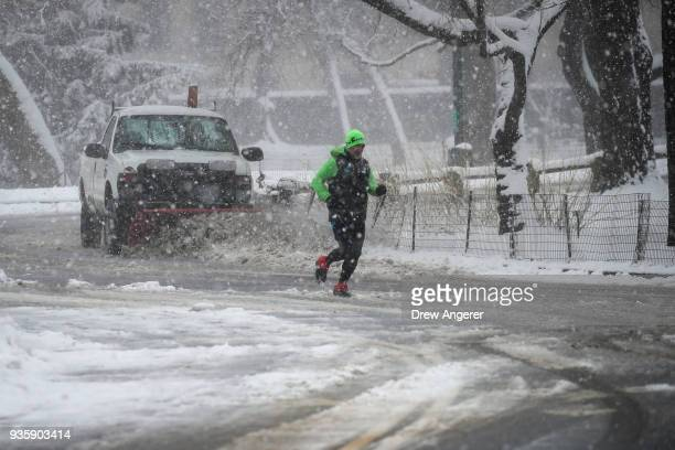 A jogger run ahead of a snow plow in Central Park during a snowstorm March 21 2018 in New York City The fourth nor'easter in three weeks hit the city...