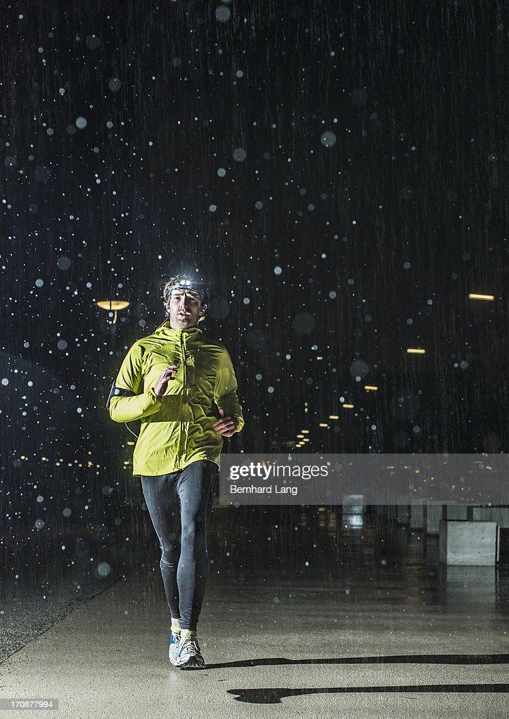 Jogger running in the rain, at night : Stock Photo