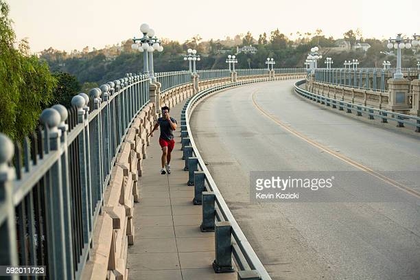 jogger running on bridge, arroyo seco park, pasadena, california, usa - pasadena california stock photos and pictures