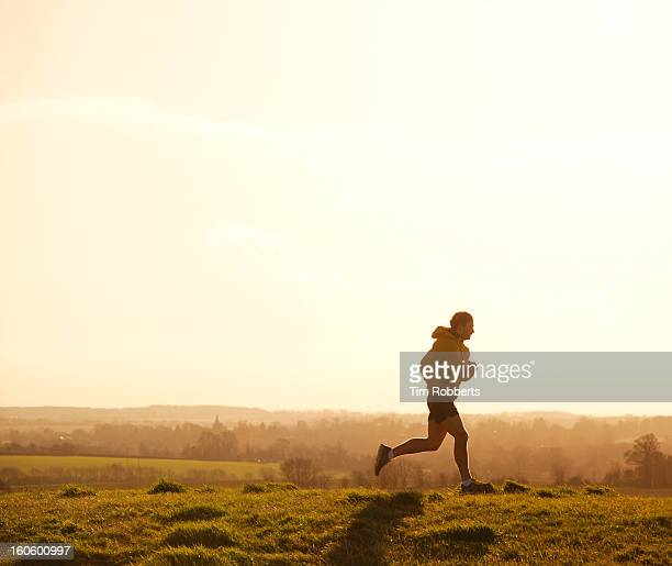 Jogger running on hill at sunset.