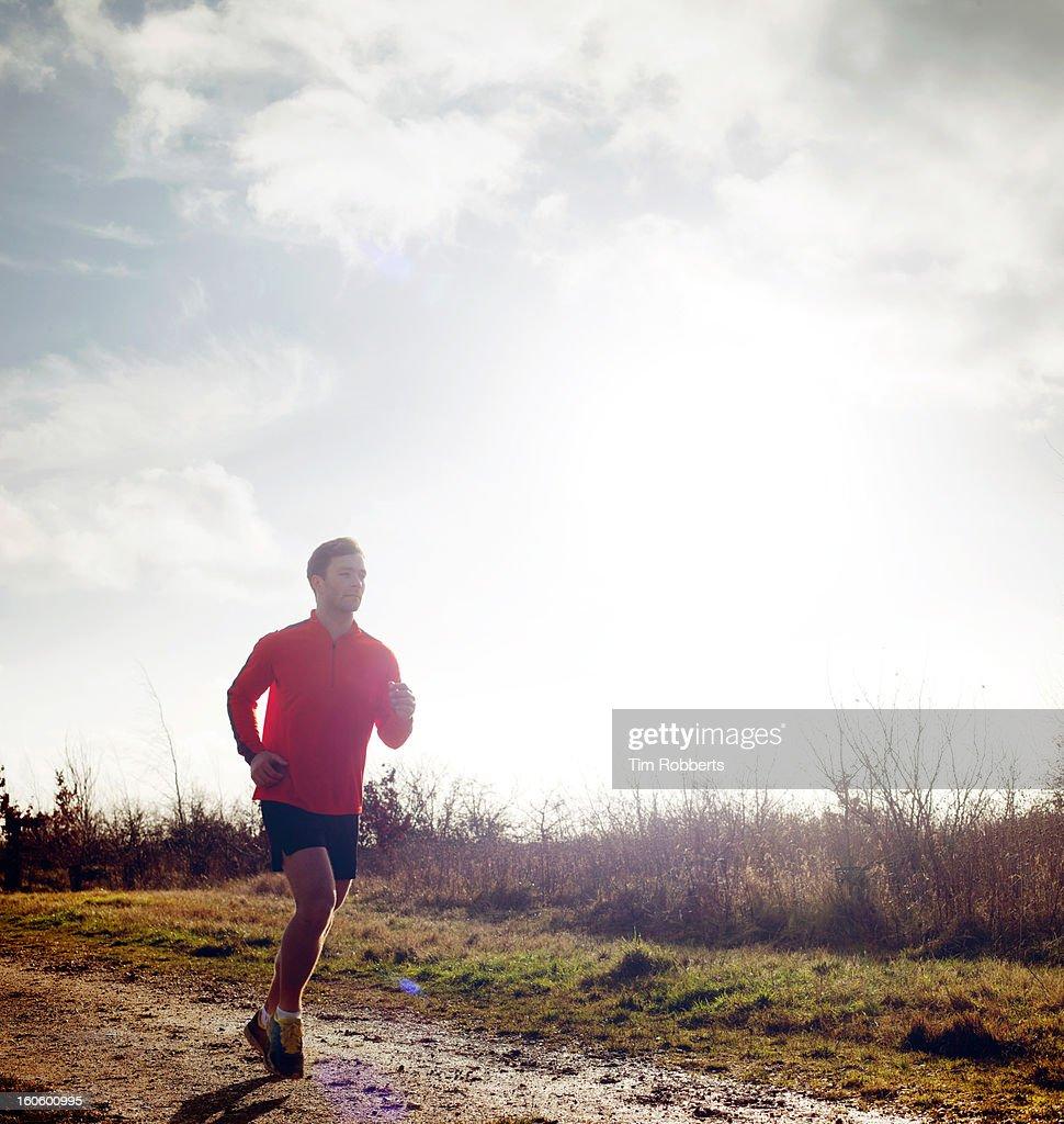 Jogger running on muddy track. : Stock Photo