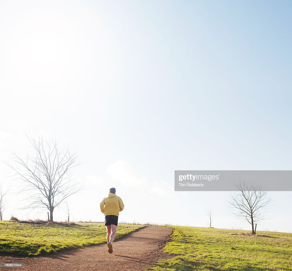 Jogger running up hill. : Stock Photo