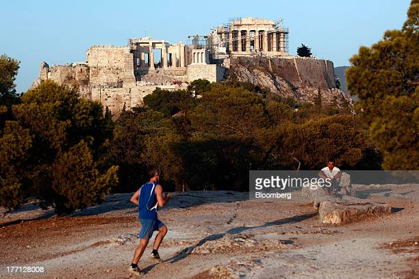 A jogger runs across parkland near the Parthenon temple on Acropolis Hill in Athens Greece on Tuesday Aug 20 2013 A third aid program for Greece...