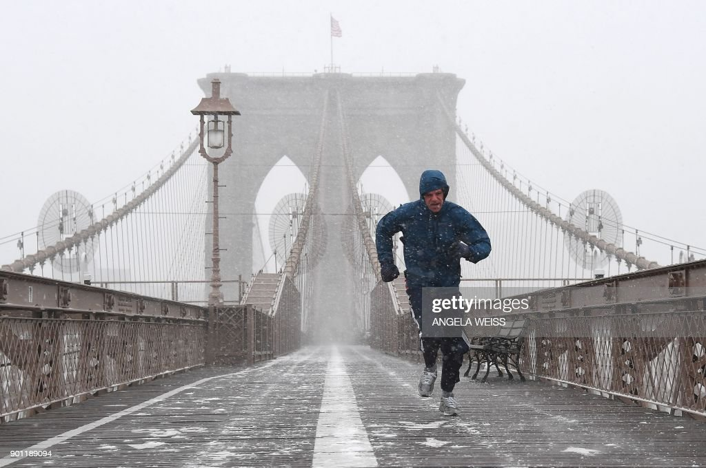 A jogger runs across the Brooklyn Bridge on January 4, 2018 in Brooklyn, New York. The US National Weather Service warned that a major winter storm would bring heavy snow and ice, from Florida in the southeast up to New England and the Northeast on Wednesday and Thursday /
